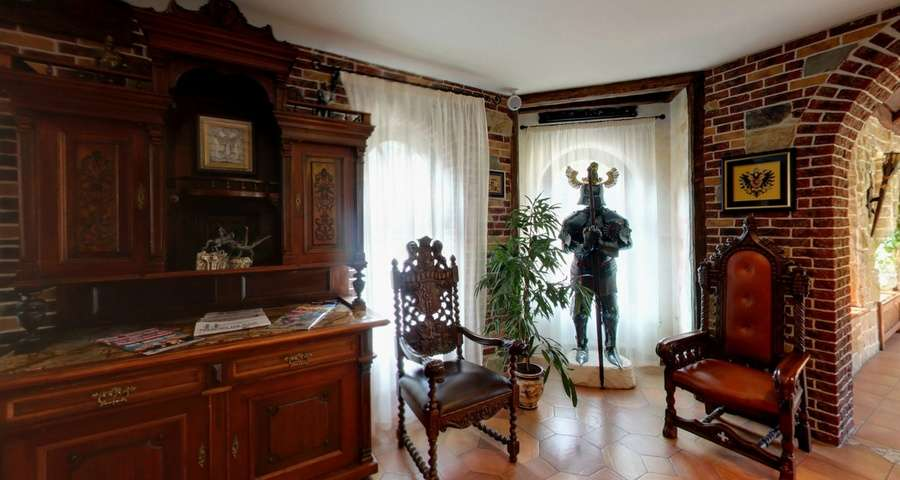 Chimney hall in the hotel Vezha Vedmezha, armor and medieval-style chairs