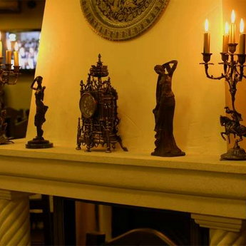 Candlesticks and figurines over the fireplace Trapezna Restaurant