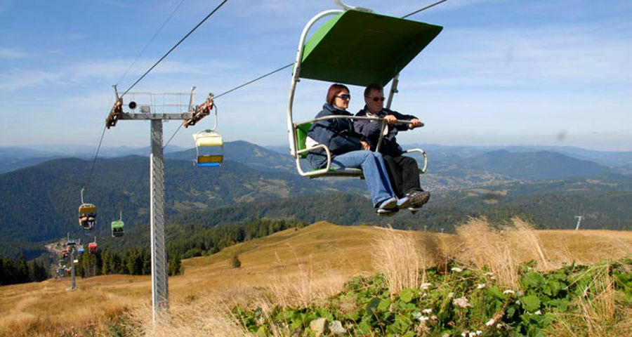 Traveling over autumn Carpathian Mountains on the chair lift